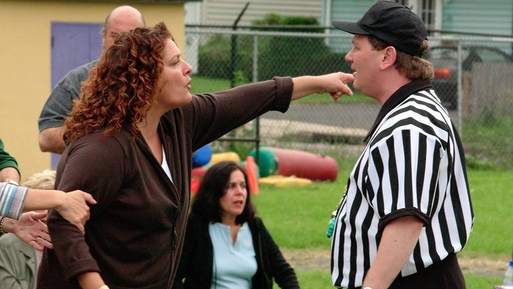 An angry mom yelling at an official during a soccer game.