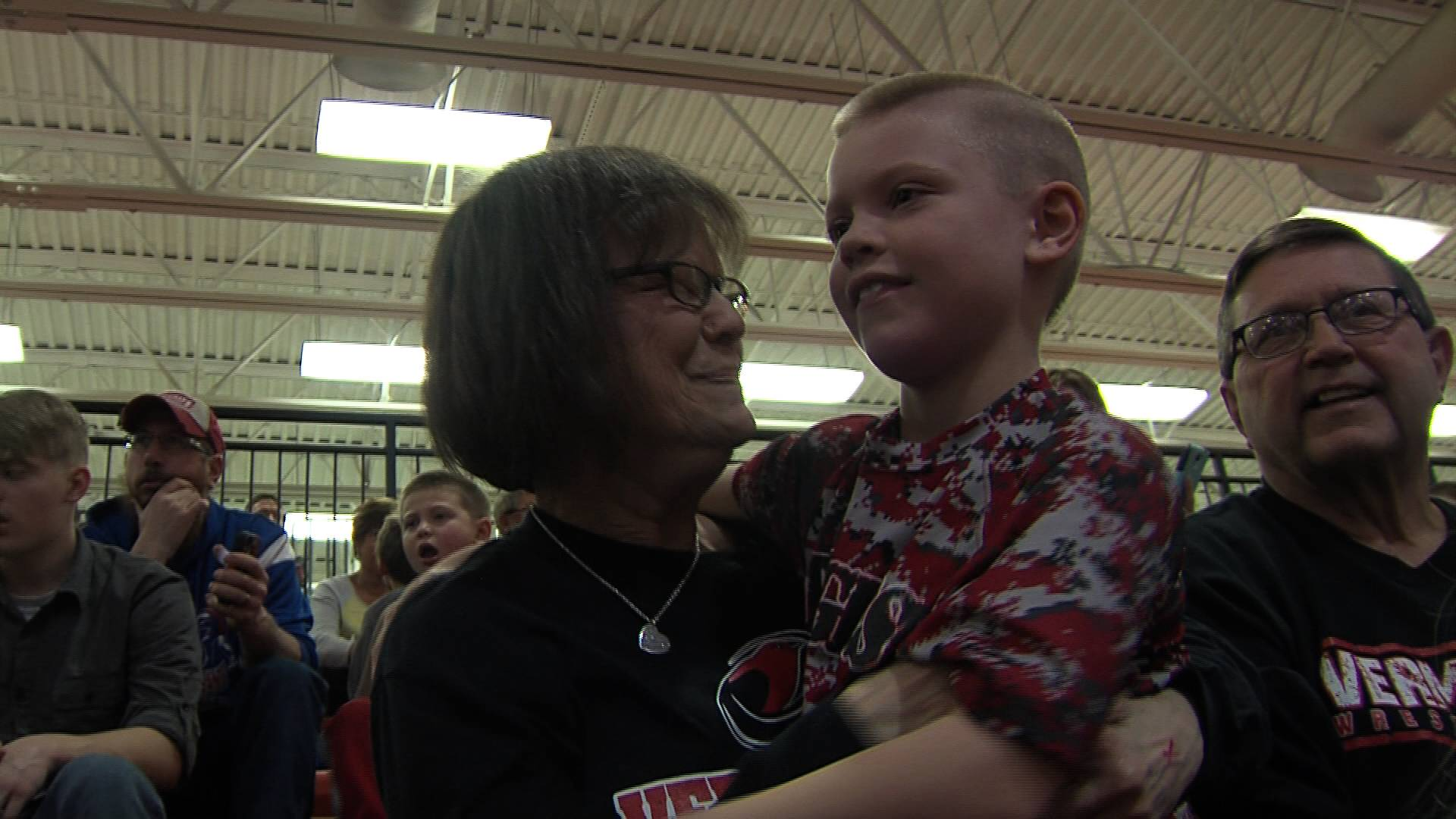 Jenny Peterson hugs her grandson Connor at a wrestling tournament