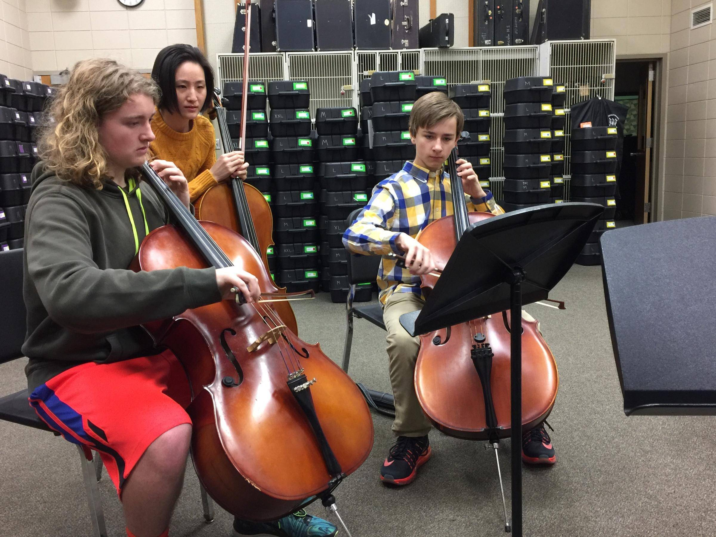 SDSO cellist Jia Cao assists students.