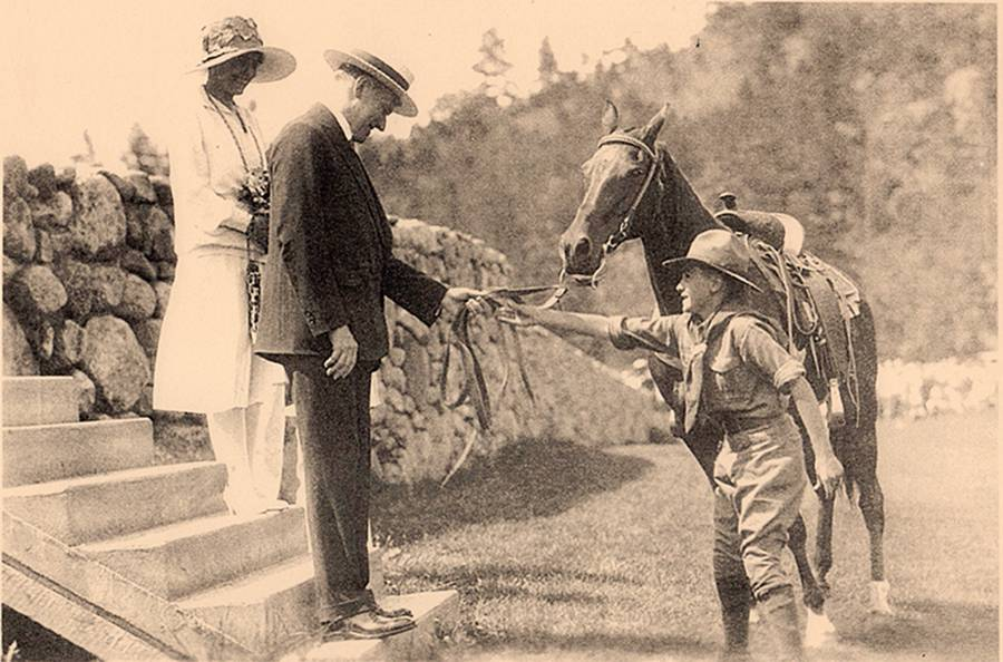 Local Boy Scout presents Coolidge with a saddle horse.