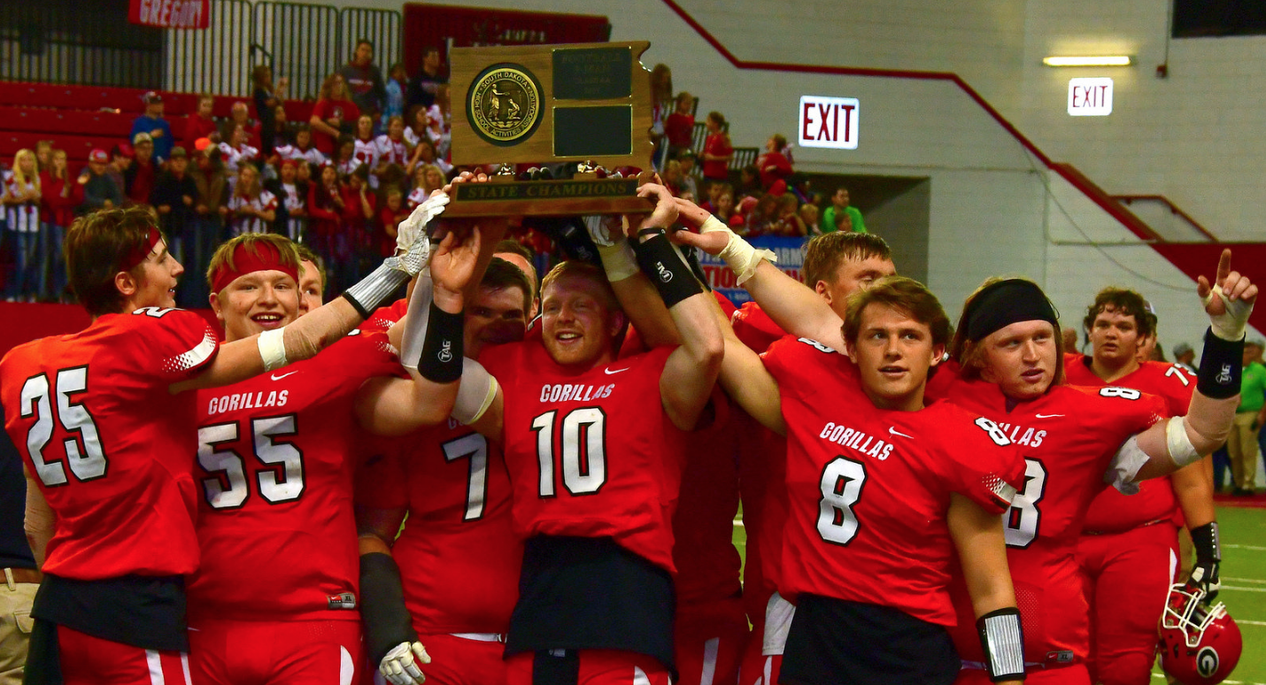 Gregory football players holding state champion trophy