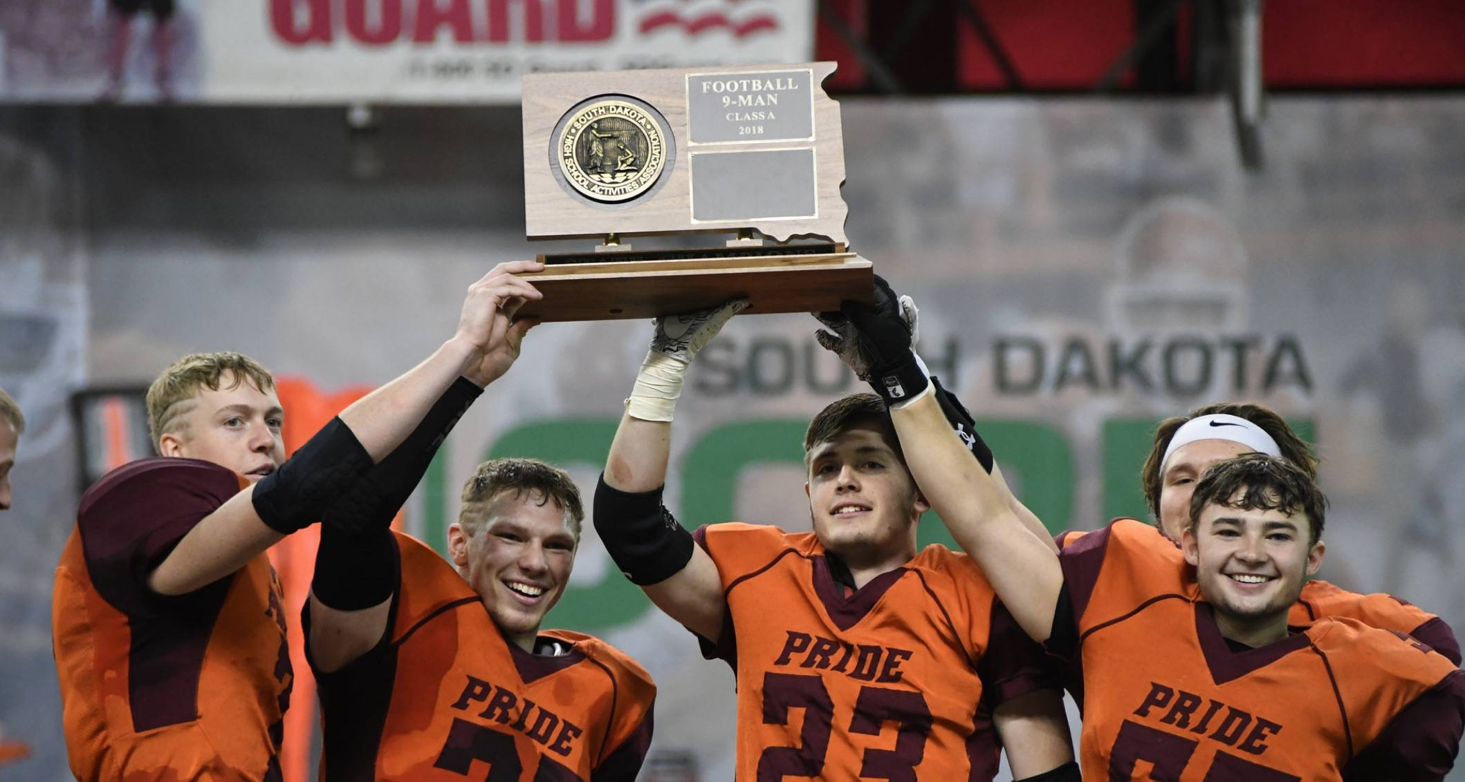 HS football players holding state title