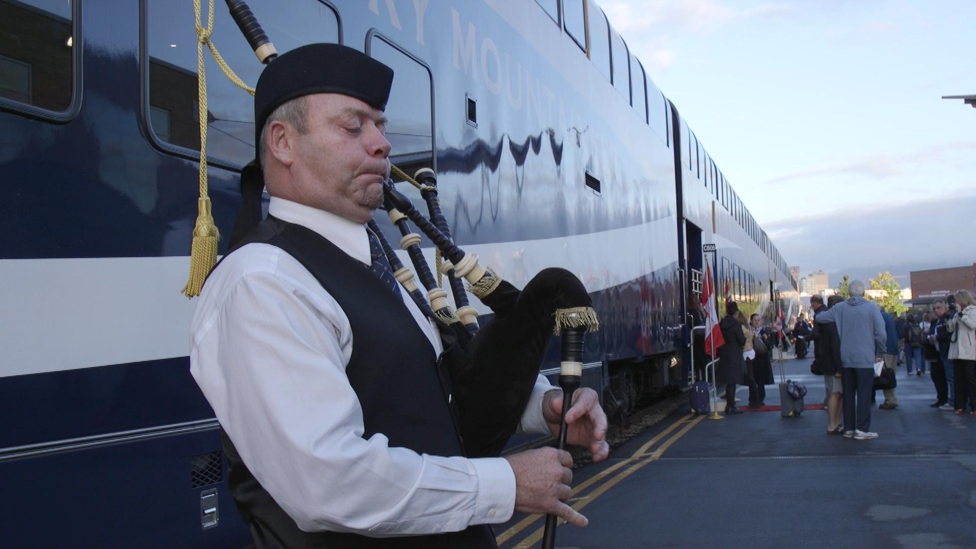 A bagpiper welsoomes passengers