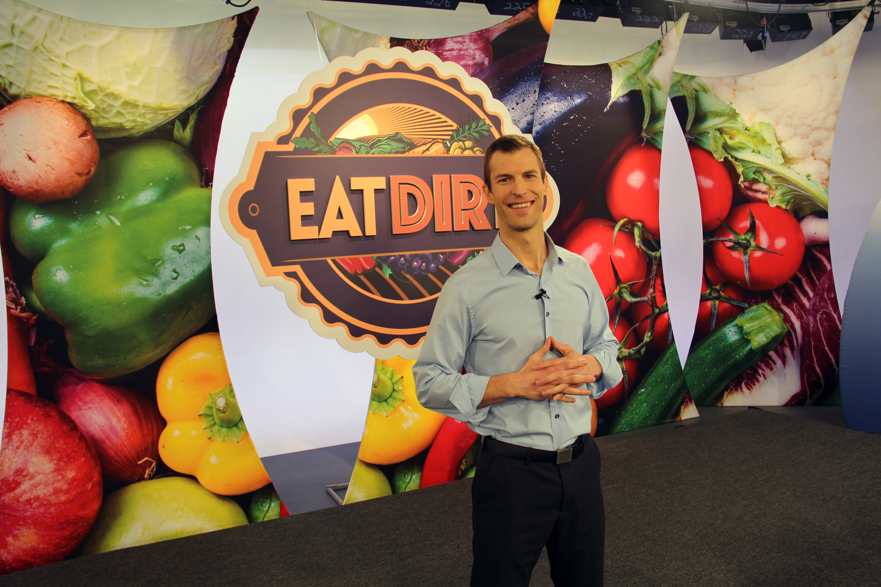 "Man stands in front of sign that says ""Eat Dirt"""