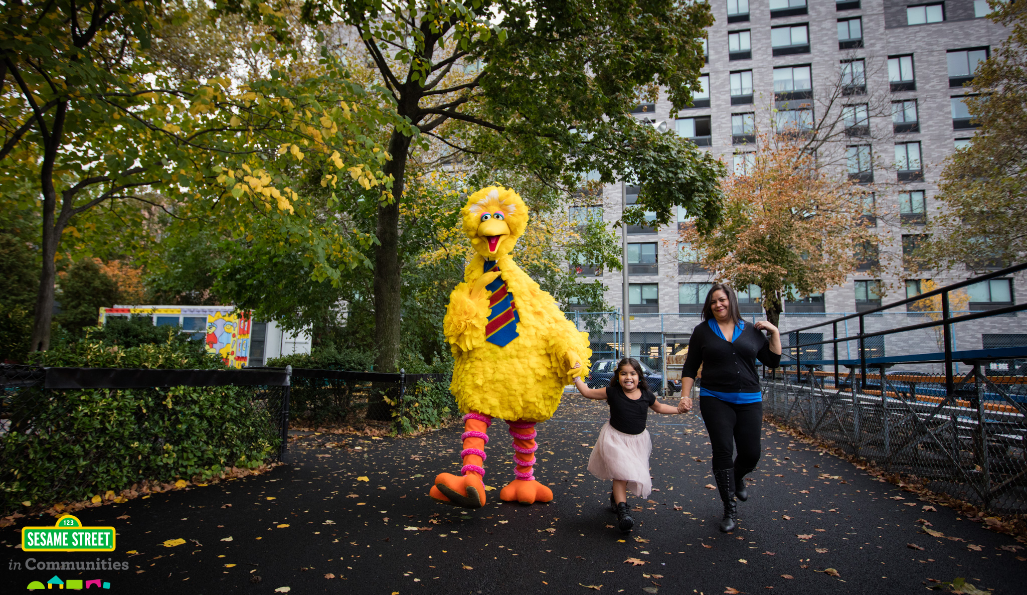 Big Bird walks alongside girl and mom.