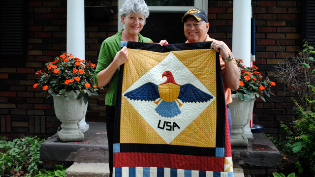 USA quilt held by woman and veteran