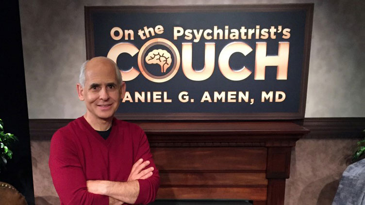 "Man smiles in front of sign that reads ""On the Psychiatrist's Couch"""