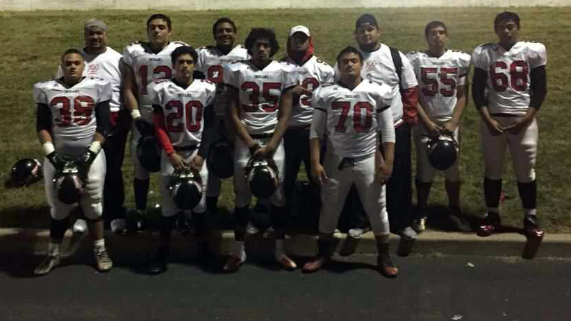 Players on a football team pose for a picture after a game