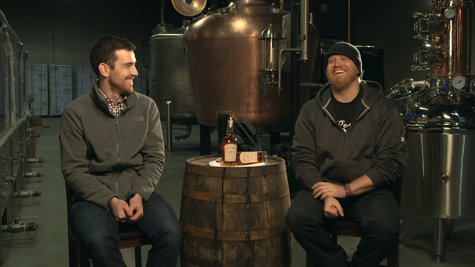 Two men sit in a distillery laughint. A barrel sits between them, and two bottles of alcohol are on the barrel.