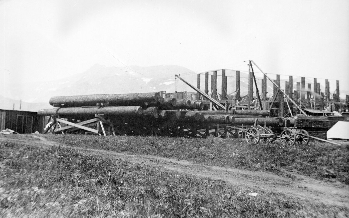 Huge logs used for construction of the Glacier Park Lodge are near a specially built siding with derricks construction materials and a freight wagon - 1911-1912