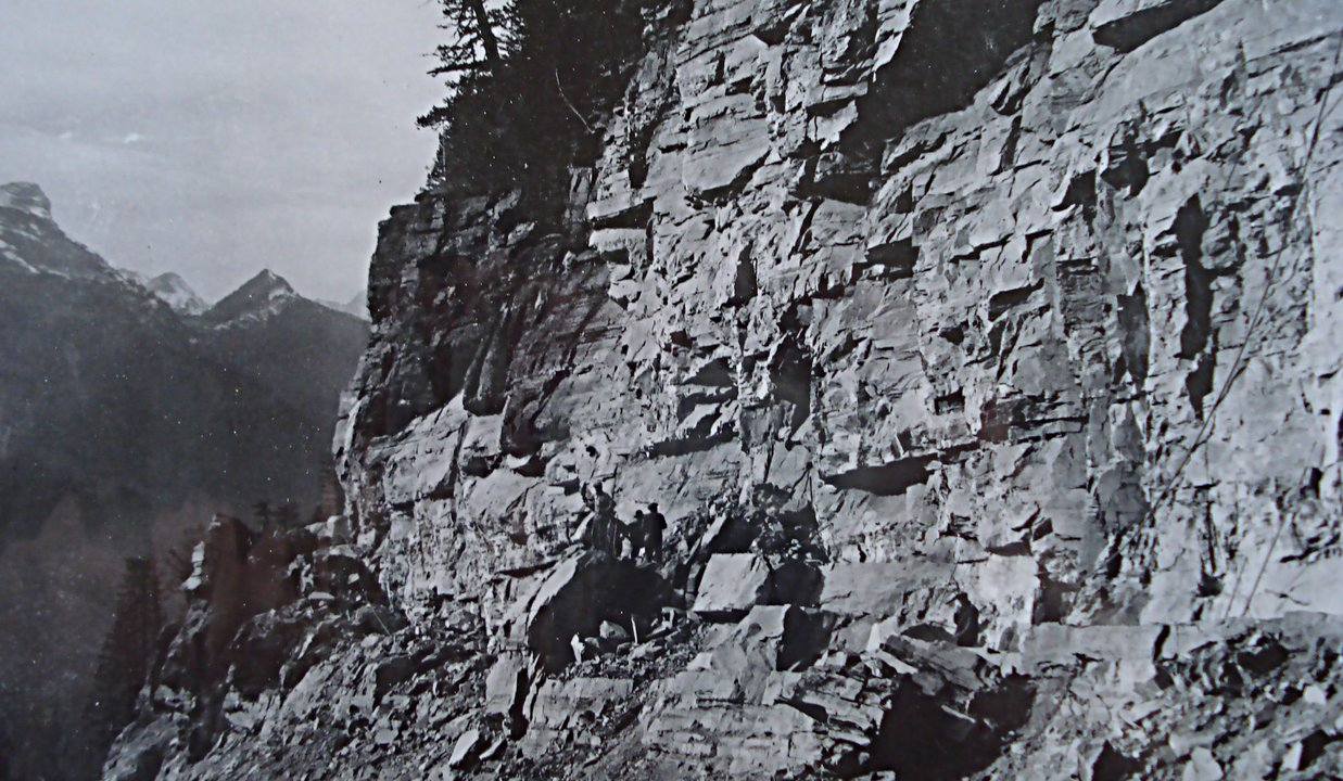 Men on rocky ledge - Going To The Sun Road construction Credit: Glacier Park Archives
