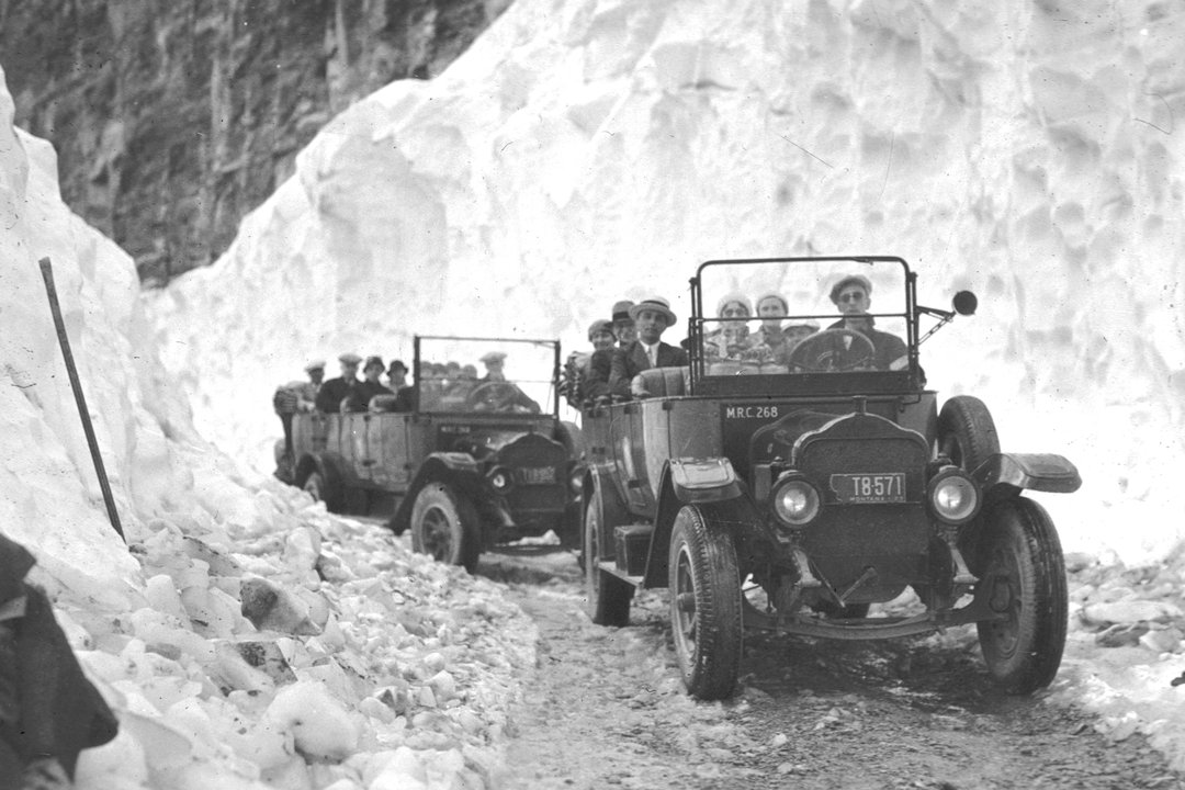 Old cars driving through snow banks - the big drift Credit: Glacier Park Archives