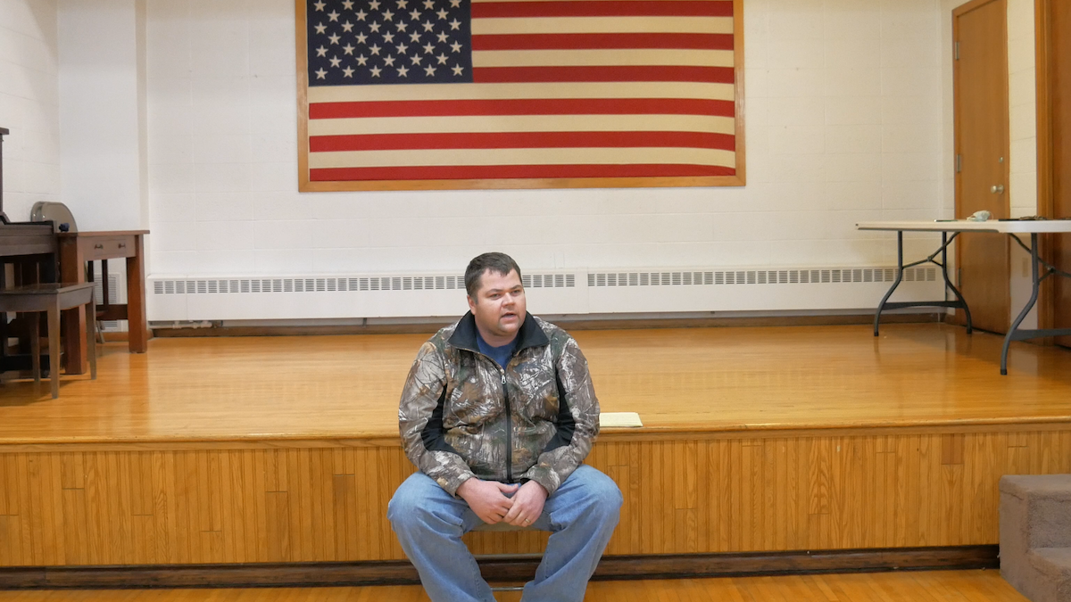An image of Murdock Mayor Craig Kavanagh sitting in City Hall in front of a USA flag.