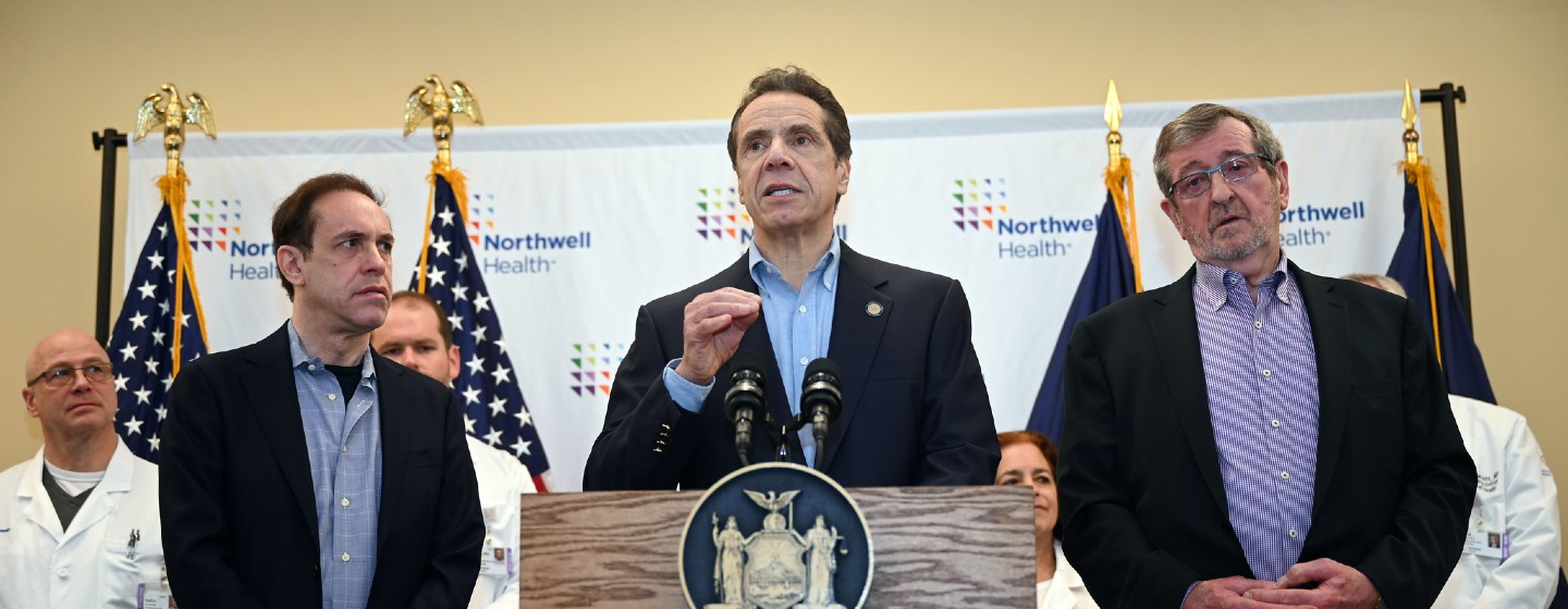 Governor Andrew Cuomo speaks to reporters with 6 individuals standing behind him