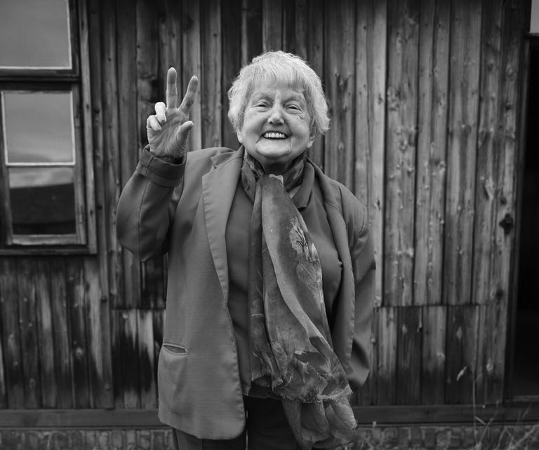 Eva Kor gives the peace sign at Auschwitz.