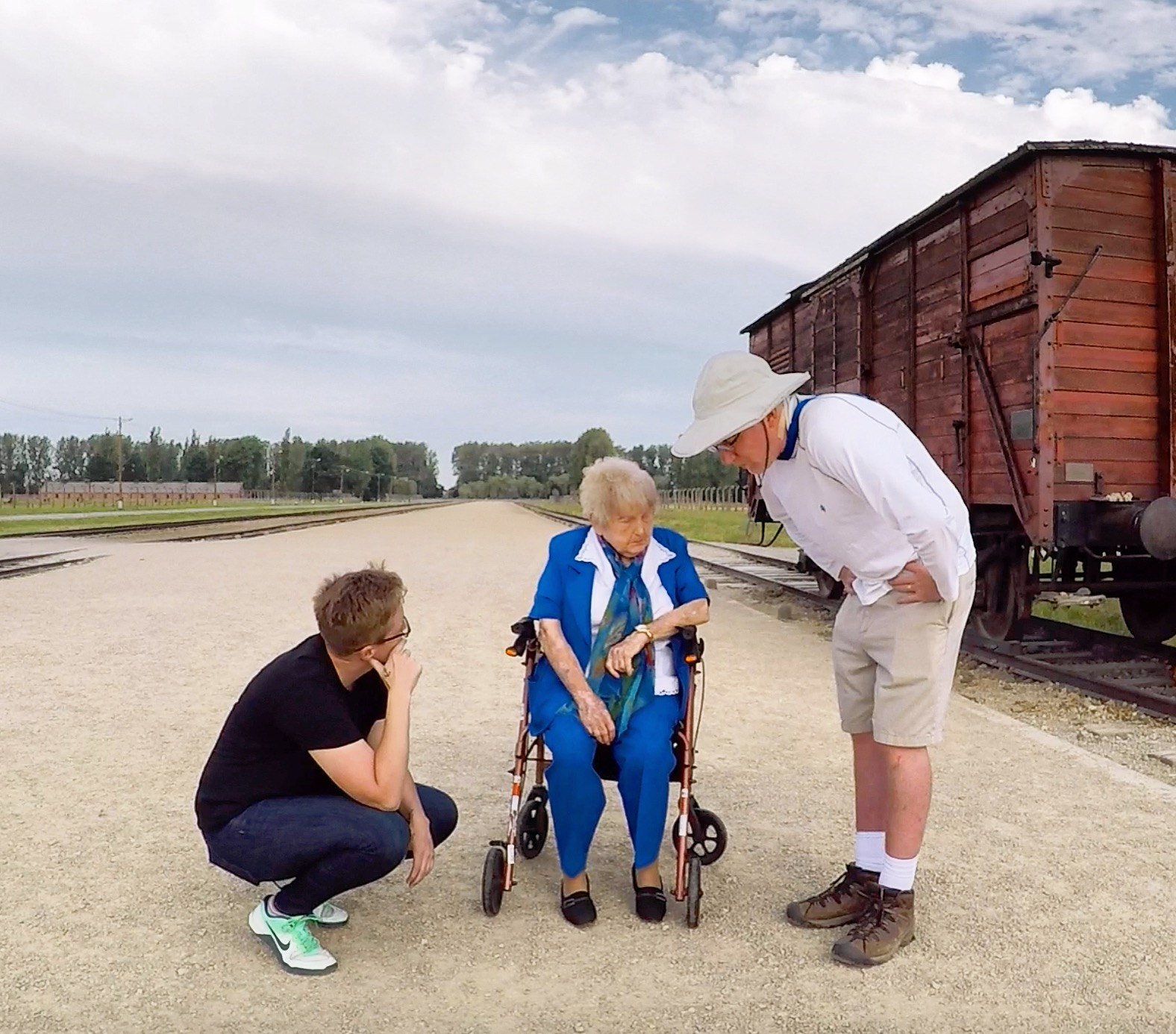 Filmmakers Ted Green and Mika Brown kneel to talk with Eva Kor at Auschwitz.