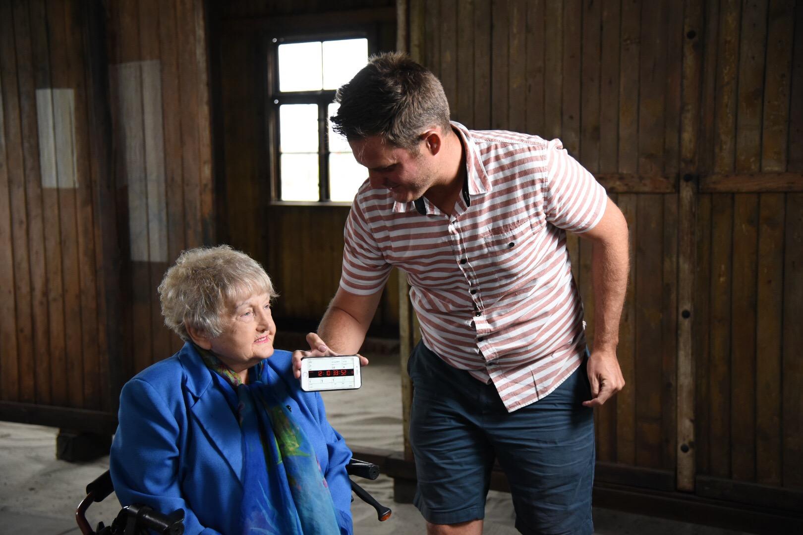 Behind the scenes, the film crew checks lighting on Eva Kor.