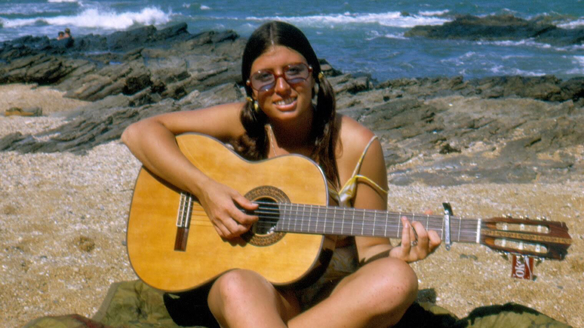 Image of woman playing a guitar on a beach