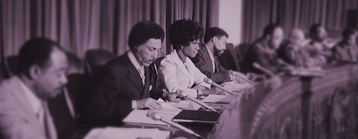 Congresswoman Shirley Chisholm sits attentively at a congressional hearing.
