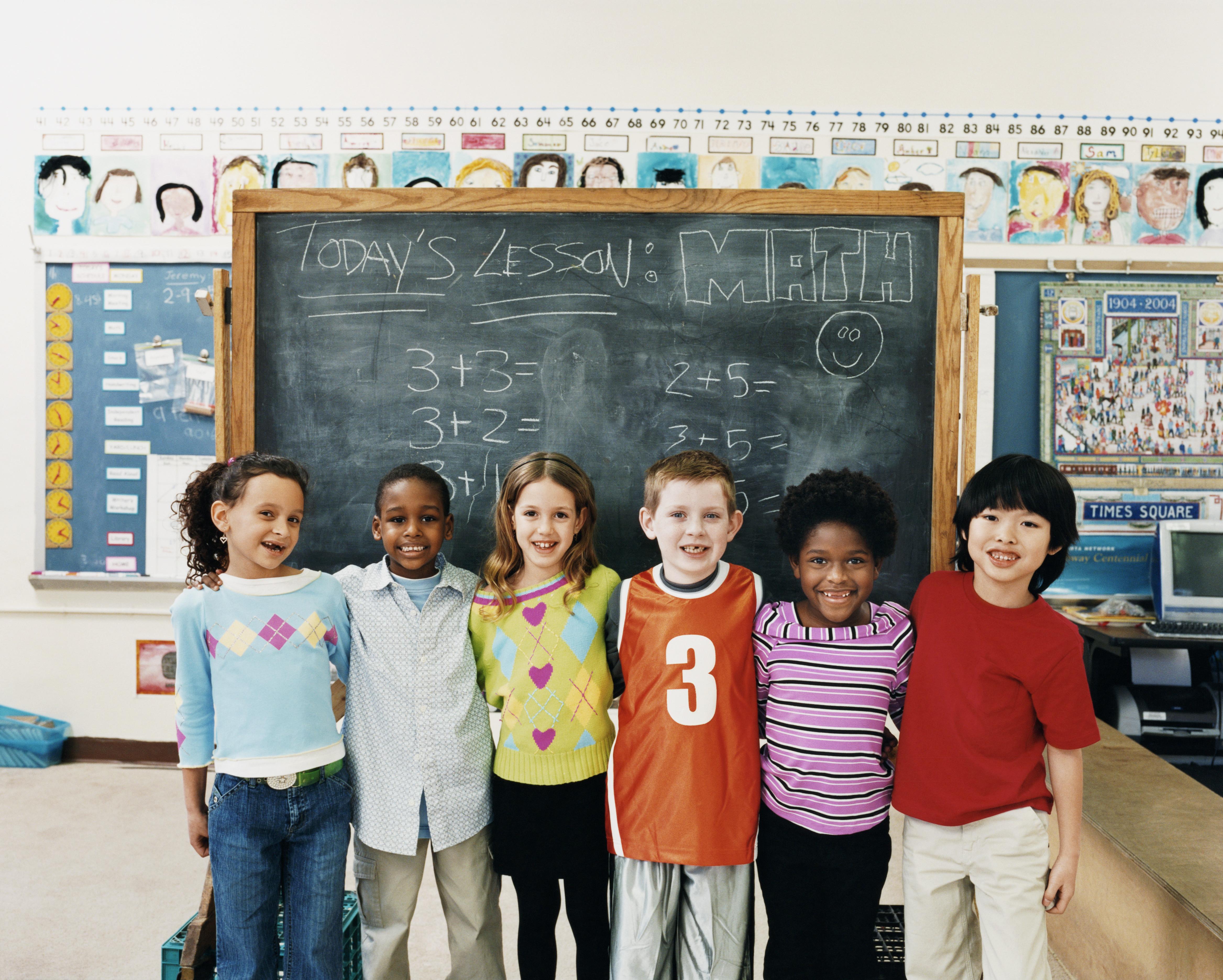 Chirldren in school in front of blackboard