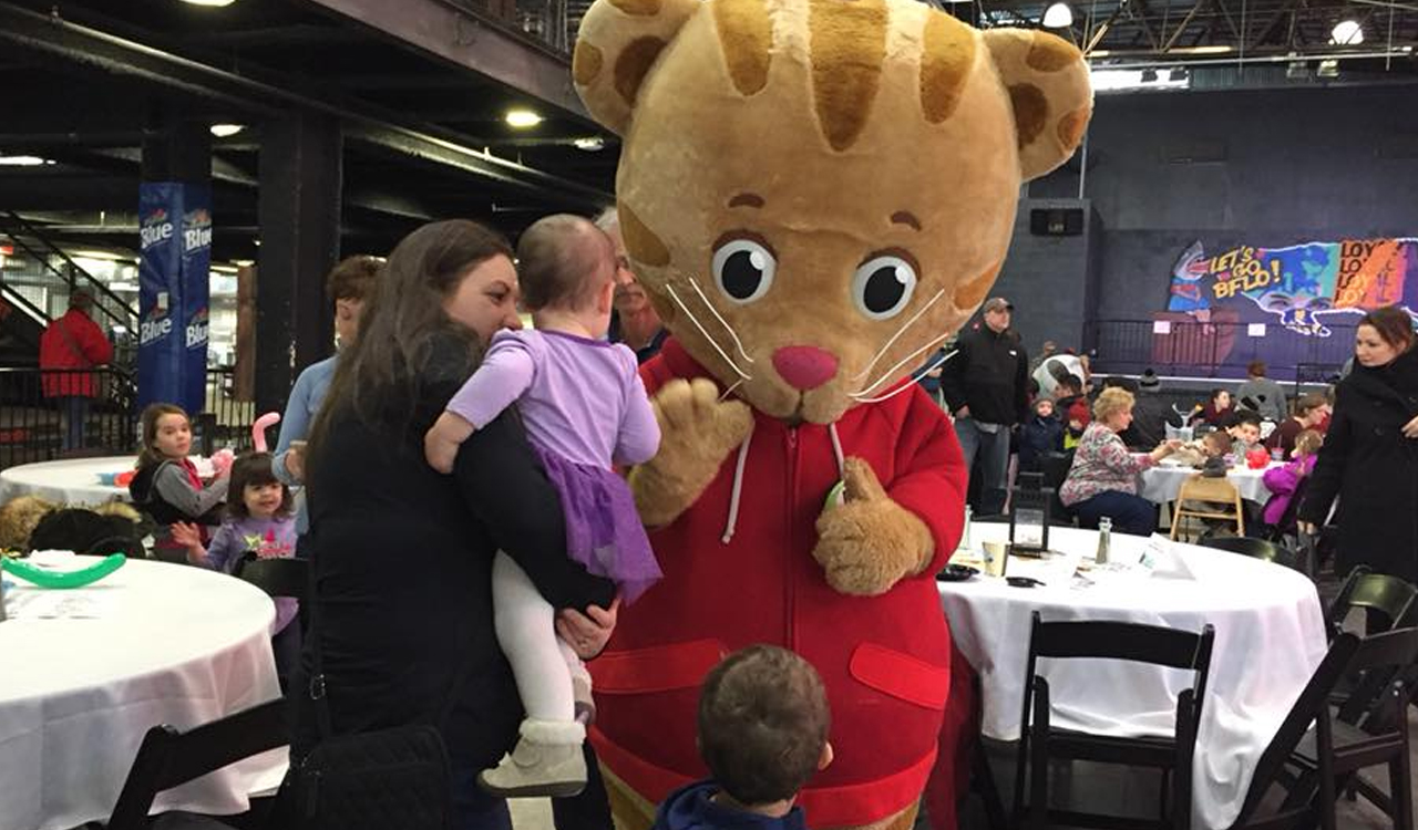 Daniel Tiger greets a young fan at the Character Breakfast