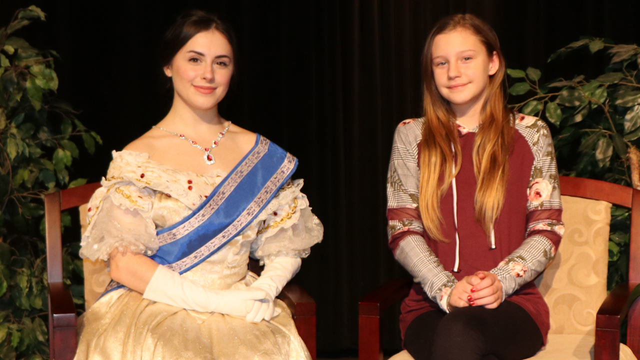 A local actress portrays Queen Victoria posing with a fan
