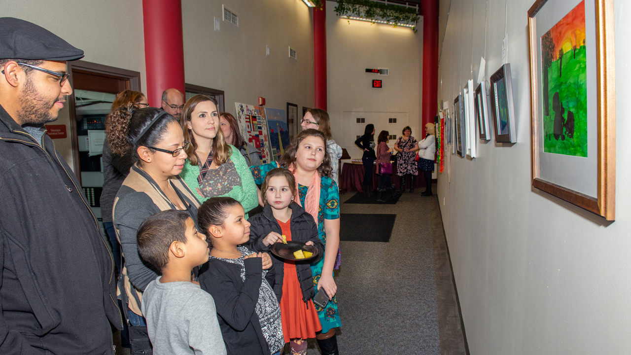 Young artists and their parents proudly view artwork
