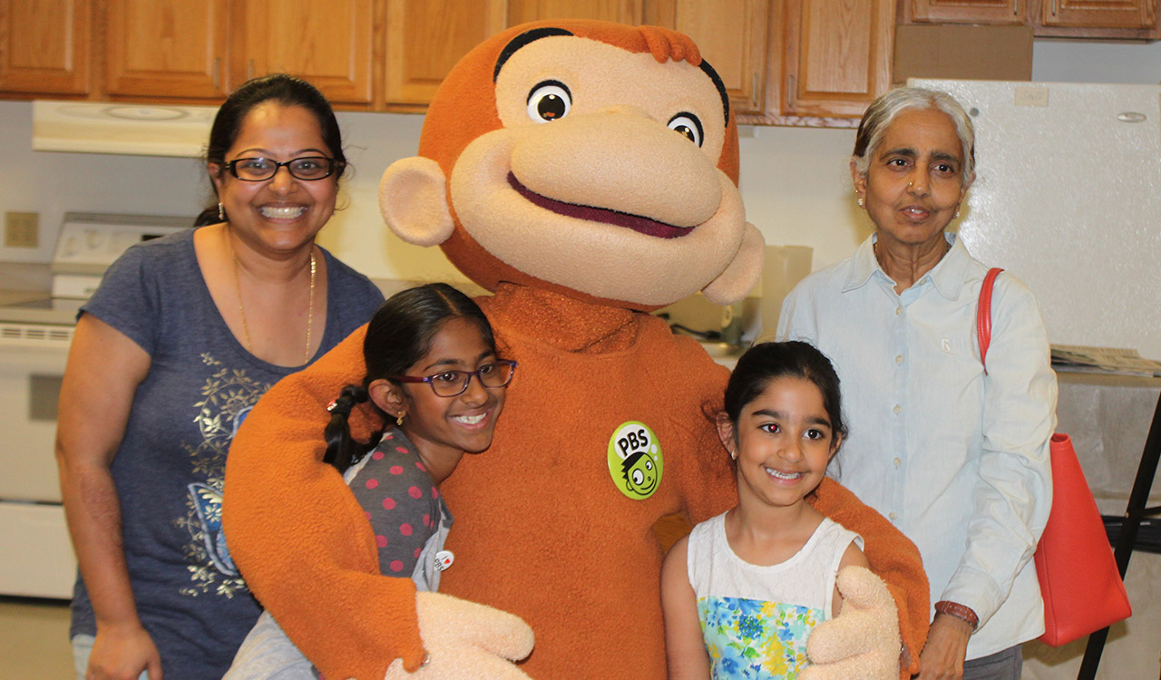 Family mingling with Curious George in the kitchen before 2017 Writers' Contest Event