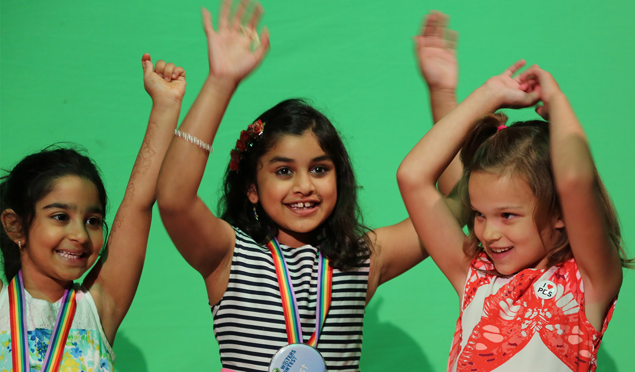 Three Writers Contest Winners laughing in front of green screen at 2017 Event