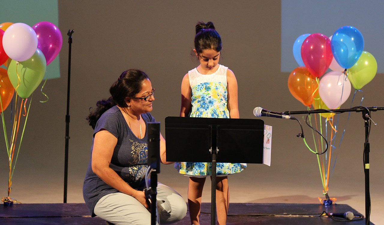 Contest Winner reads her story onstage with mom