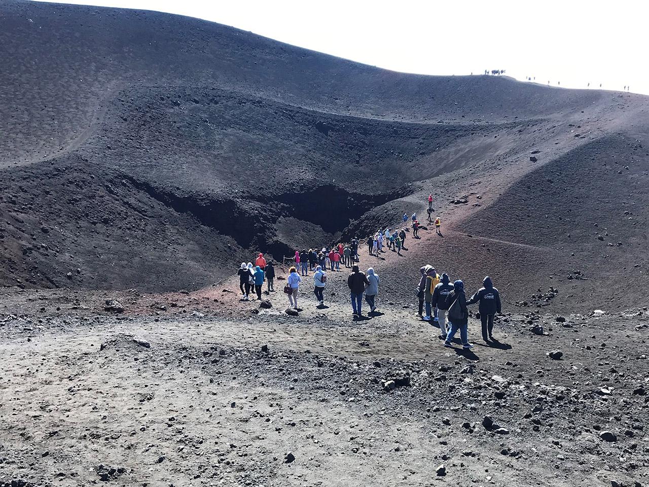 Wide shot of Travels walking up rocky slope