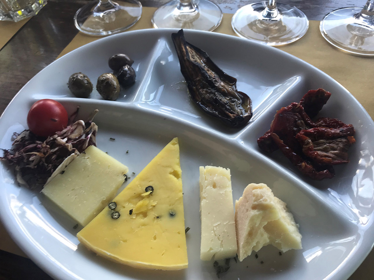 plate with various cheeses and other food.
