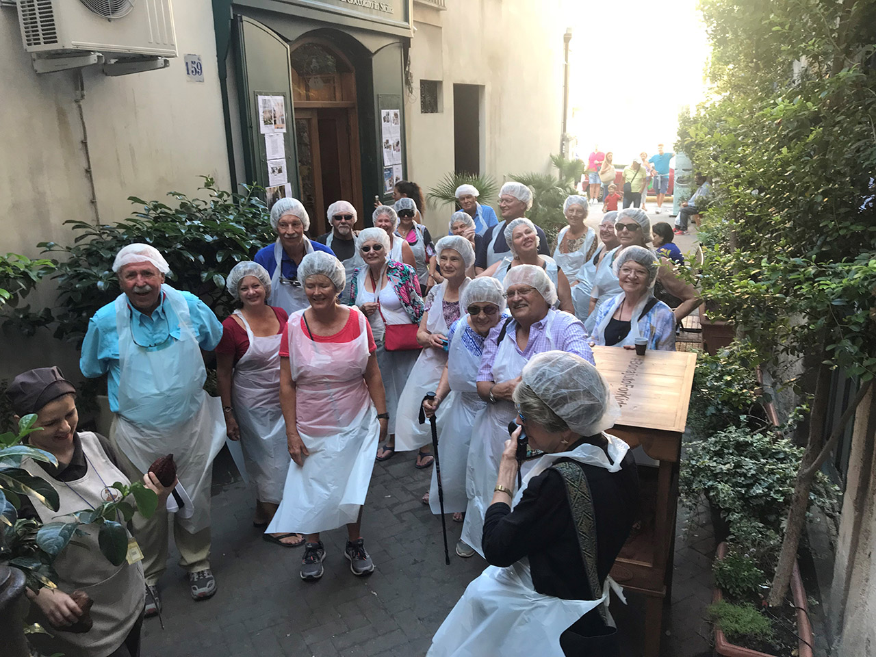 Travelers in group dress with white plastic aprons and hair caps